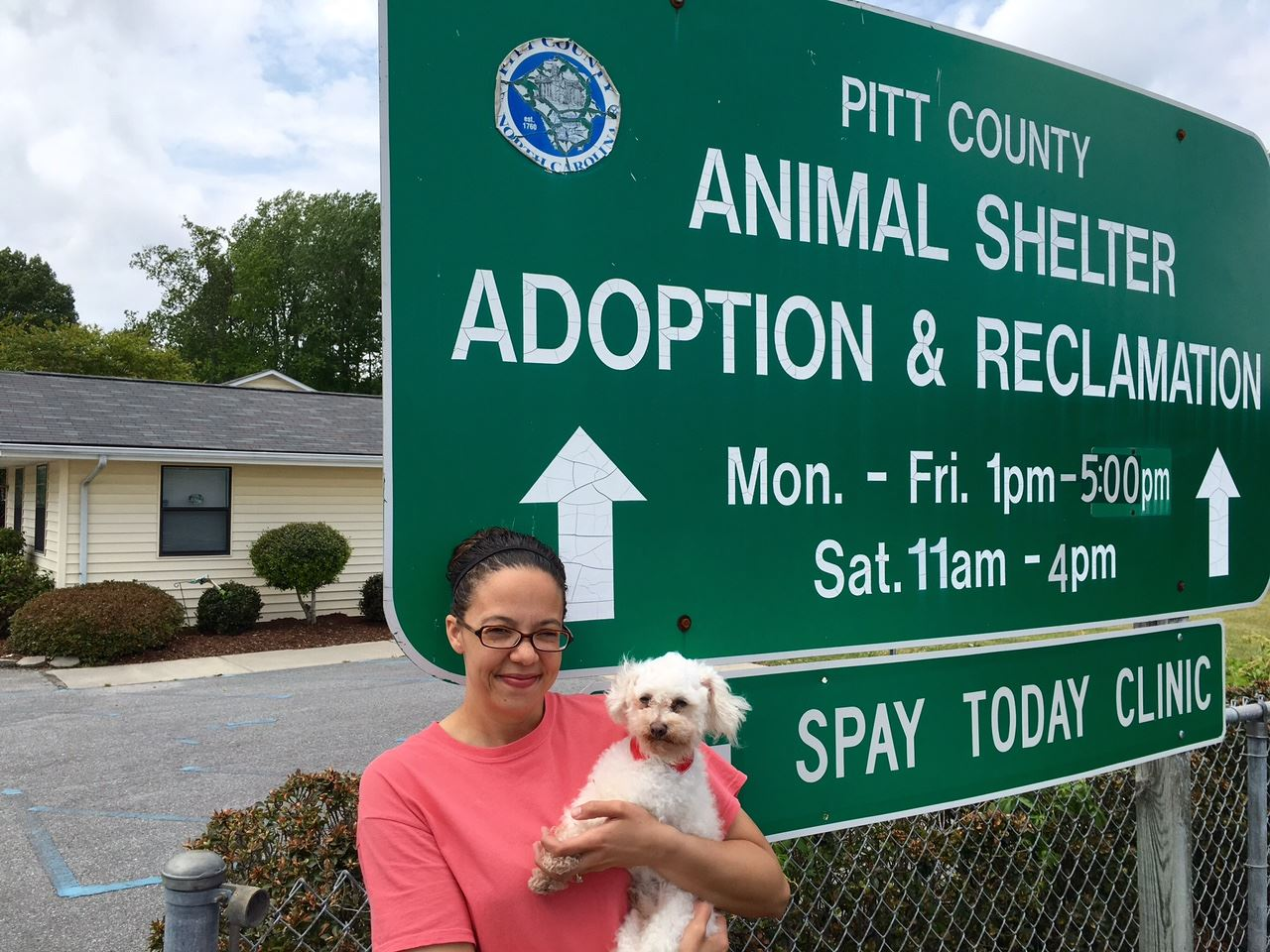 Employee holding a dog by the shelter sign