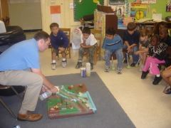 A man demonstrates an activity to children