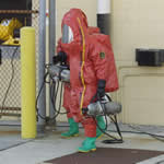 A man wearing a hazmat suit carrying two tanks