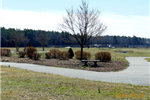 A paved walking trail with shrubbery and benches and a field behind it